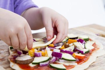 small hands preparing pizza