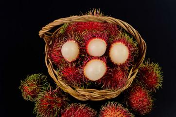 Rambutan in basket on a black background Fototapete