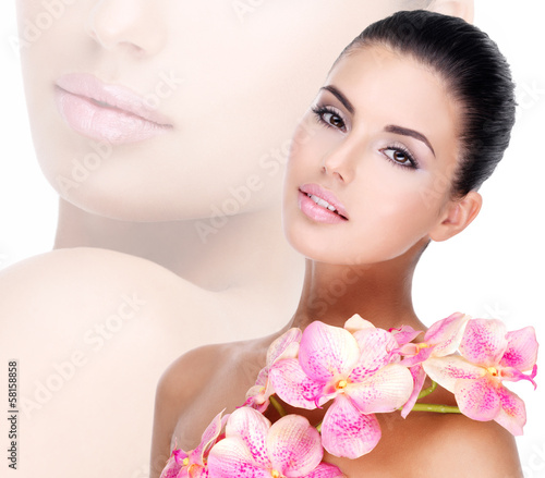 Wall mural Beautiful face of  woman with healthy skin and pink flowers