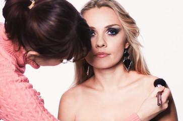Visagiste doing makeup for model