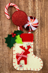 Christmas decorations and sock on wood background