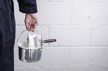 Painter, decorator holding paint bucket with brush