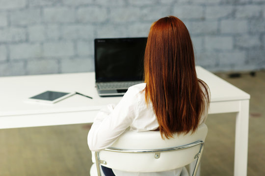 Picture from behind of a businesswoman sitting at her desk