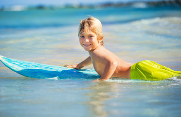 happy young boy in the ocean on surfboard