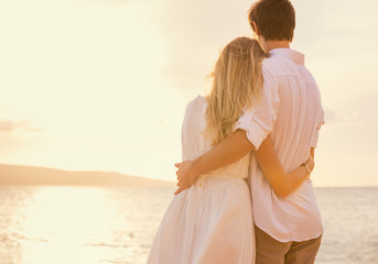 Happy romantic couple on the beach at sunset embracing each othe