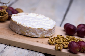 cheese, walnuts, grapes, on a chopping board on an old table