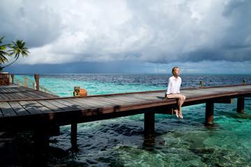 Girl is relaxing on a pier in the ocean