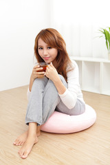 Young woman at home sipping tea