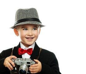 Little boy in hat and black jacket with vintage camera