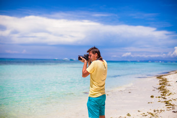 Young man photographing with a camera in his hands on a tropical