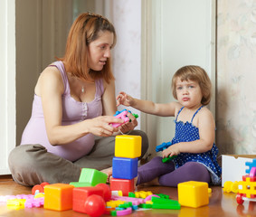 mother plays with child in home