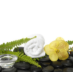 roller towel with green fern and orchid, candle on pebbles