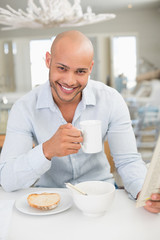 Smiling man drinking coffee while reading newspaper at home