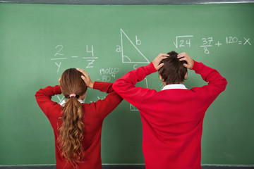 Confused Schoolchildren Standing Against Board
