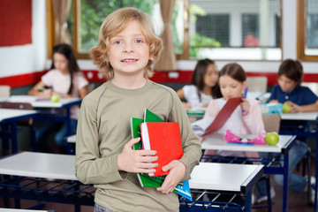 Schoolboy Holding Books With Classmates In Background