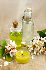 massage oil with and spring flower with candle on board