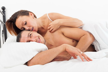 Middle-aged lovers kissing in bed