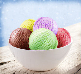 Colorful ice-cream scoops in white cones.