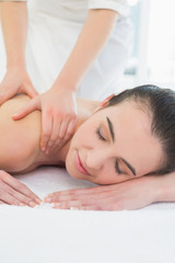 Beautiful woman enjoying shoulder massage at beauty spa