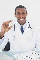 Smiling doctor holding a prescription bottle in medical office