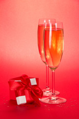 Two glasses with champagne and small gift box