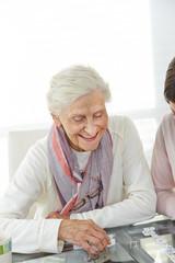 Seniorin spielt Domino im Seniorenheim