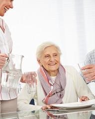Wall Mural - Pflegehilfe gießt Senioren Wasser ein