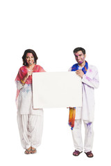 Couple celebrating Holi and holding a blank placard