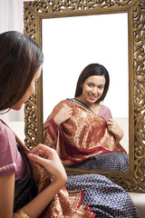 Reflection of a woman in mirror trying a sari on herself