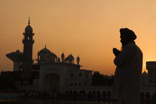 Silhouette of praying sikh man at golden temple of Amritsar, Ind