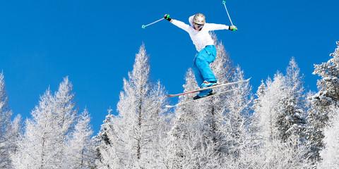 salto con sci fra alberi innevati