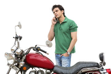 Man standing beside a motorcycle and talking on a mobile phone