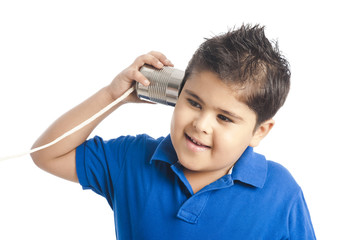 Close-up of a boy listening to a tin can phone