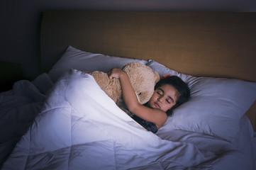 Girl sleeping on the bed with a teddy bear