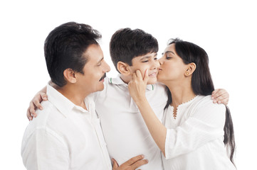 Close-up of a couple kissing their son