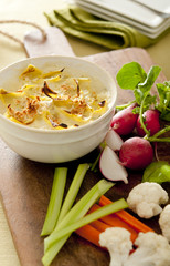 Closeup of freshly baked artichoke dip with vegetables.