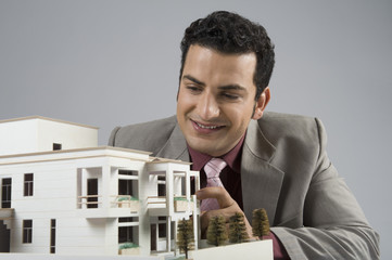 Businessman looking at a model home in an office