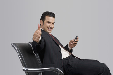 Businessman holding a mobile phone and showing thumbs up sign