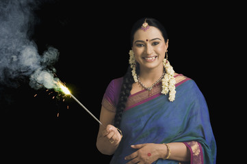 Woman celebrating Diwali festival with a sparkler