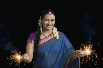 Woman celebrating Diwali festival with sparklers