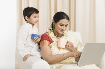 Woman using a laptop with her son and having coffee