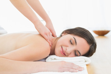 Beautiful woman enjoying neck massage at beauty spa
