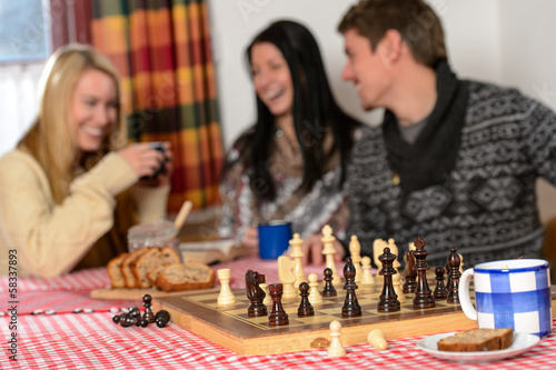 Playing chess winter chalet friends laughing