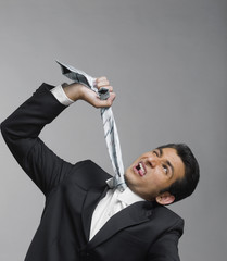 Close-up of a businessman strangling himself with necktie