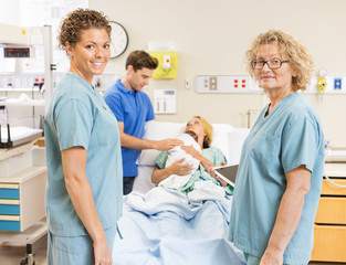 Smiling Nurses Standing Against Couple With Baby In Background