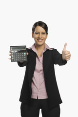 Businesswoman holding a calculator and showing thumbs up sign