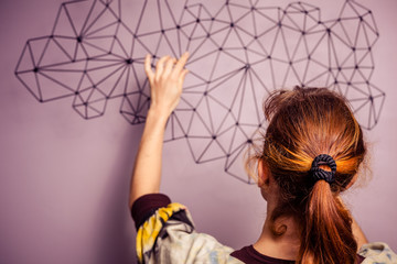 Young woman hanging a piece of art on her wall