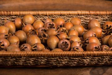 Medlar Fruits in Tray on Wooden Board