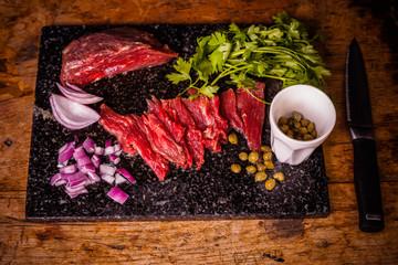 Steak tartare ingredients on chopping board