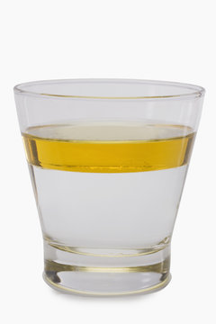 Oil floating on water surface in a glass